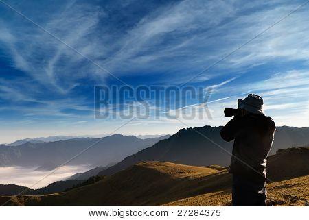 Um cinegrafista standed e tiro com nuvens no ar livre.