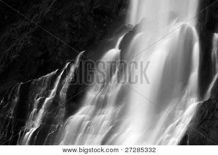 It is dramatic blurred view of waterfall flowing over rocks.