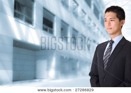 Asian young business man standing and looking in front of office buildings.