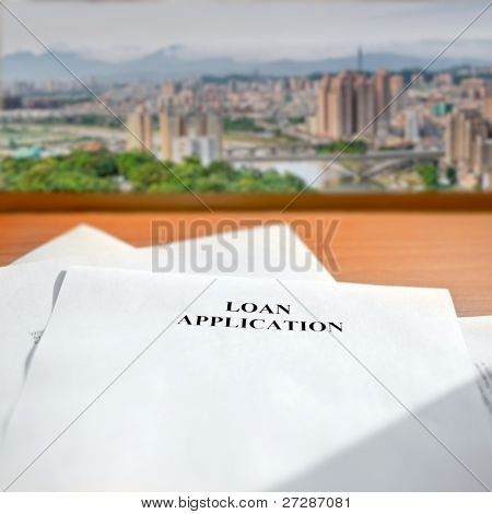 Loan application paper on desk near window and cityscape far away.