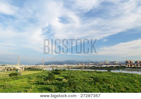 Cityscape with green forest under dramatic blue sky and white clouds in Taipei, Taiwan, Asia.
