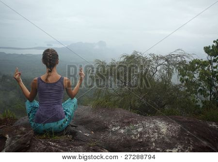 Young woman relaxing on top of a mountain with view to valley. Rainy weather, wet clothes.