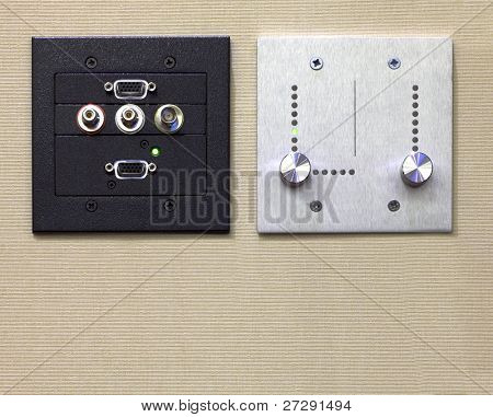 Two control panel for computer and light with ports and switches on beige wall