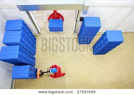 Aerial view of two workers working with  plastic blue boxes in small warehouse