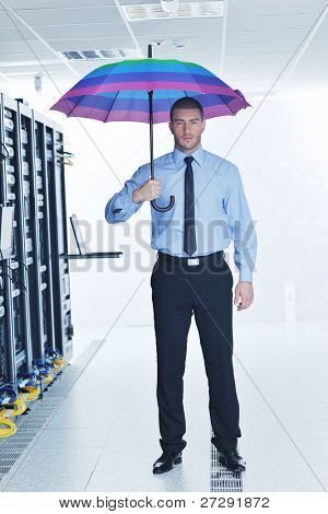 young handsome business man  engineer in .businessman hold  rainbow colored umbrella in server datacenter room  and representing security and antivirus sofware protection concept