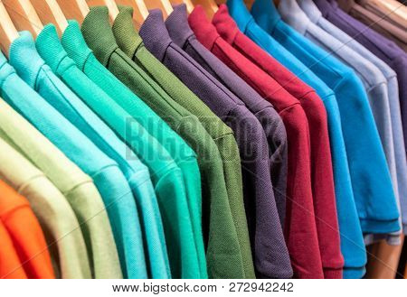 poster of Vibrant Shirts On Hangs For Sale In Shop. Multicolored Polo On Wooden Hanger. Summer Fashion In Depa