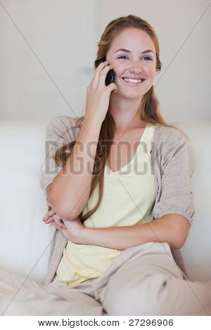 Smiling young woman listening to caller on her cellphone