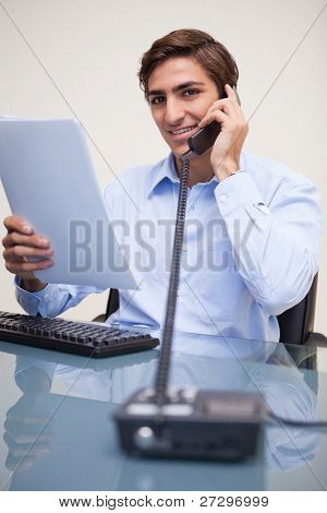 Smiling young businessman holding paperwork while on the phone