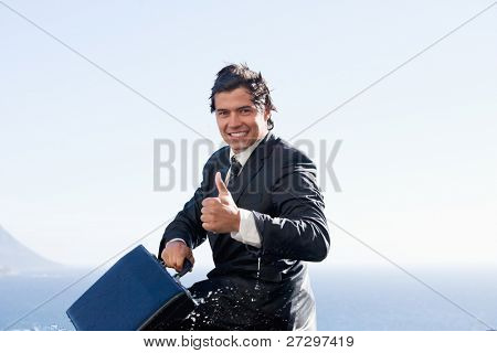Cheerful businessman with the thumb up while holding a briefcase
