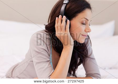 Young woman enjoying music while laying on the bed