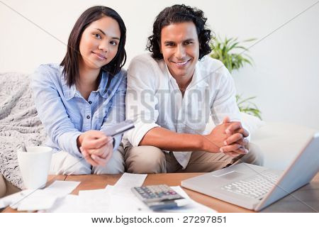 Young couple doing online banking in the living room