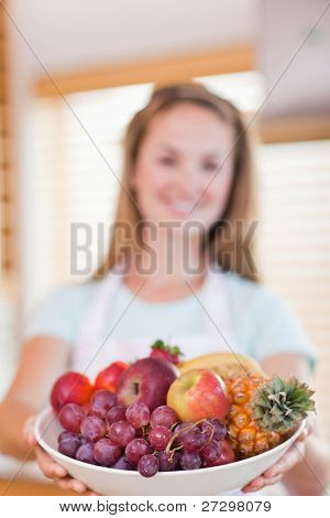 Portrait of a young woman presenting a fruit basket with the camera focus on the object