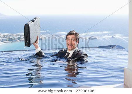 Businessman holding eine Aktentasche in einem Schwimmbad