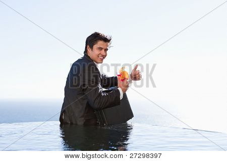 Portrait of a businessman posing with a cocktail and a briefcase in a swimming pool