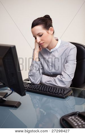 Young businesswoman sitting bored at her desk