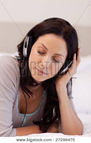 Young woman laying on her bed enjoying music