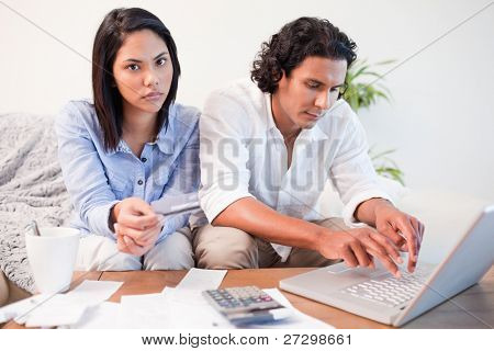 Young couple checking their bank accounts online in the living room
