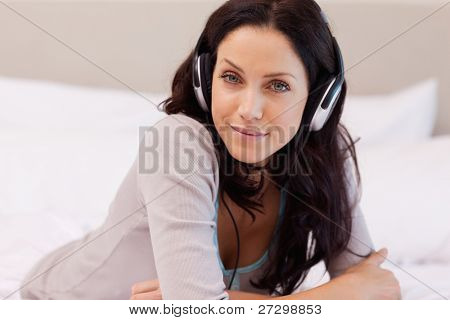 Smiling young woman enjoying music on her bed