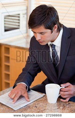 Portrait of a businessman drinking coffee while reading a newspaper in his kitchen