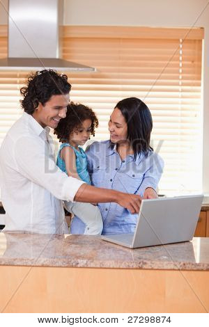 Young family using notebook in the kitchen together