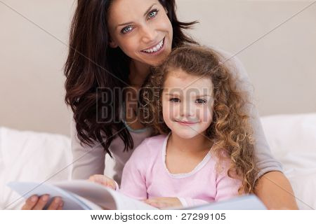 Young mother reading a book with her little daughter