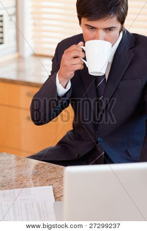 Portrait of a businessman drinking coffee while using a laptop in his kitchen