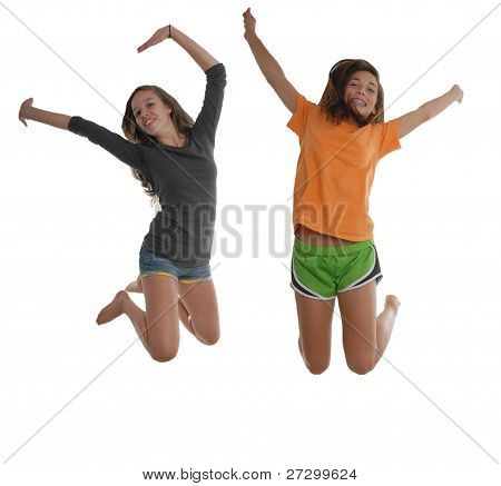 Two Happy Graceful Teenage Girls Jumping In The Air