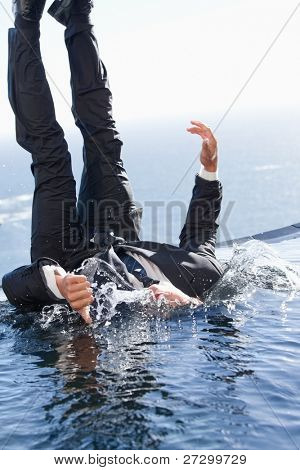 Portrait of a cheerful businessman falling into water with the thumb up