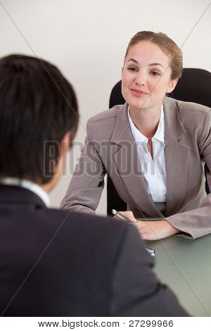 Portrait of a manager interviewing a male applicant in her office