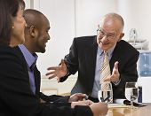 picture of business meetings  - Business team meeting with two men and a woman sitting at a desk with water - JPG