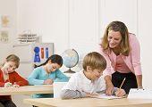 stock photo of student teacher  - Teacher helping student in classroom - JPG