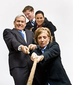 Business people playing tug-of-war