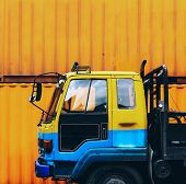 Yellow truck parked near a yellow container box poster