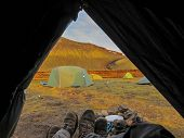 Tent Lookout With Couple Hiking Boots And Mountain View At Sunset. View From Inside A Tent At Sunset poster