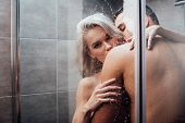 Passionate Man Embracing And Kissing Beautiful Woman In Shower poster