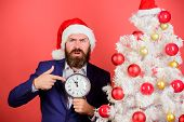 Time To Celebrate. Man Bearded Wear Suit And Santa Hat Hold Clock. Businessman Join Christmas Celebr poster