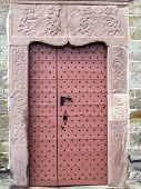 The Beautiful Old Pinkish Painted Wooden Door With Metal Rivets Of St. Peters Church In The Village  poster