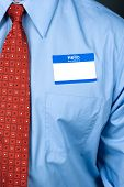 A businessman wearing a blank nametag and bright red tie with a blue shirt.