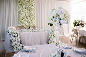 Wedding Table In Restaurant Decorated With Flowers. White Tablecloth, Crystal Glasses And Cutlery, N poster