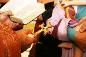 stock photo of christening  - Golden cross with gemstones in the priest hand in Christening.
