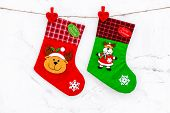 Decorative Christmas Socks. Empty Socks For Gift Hanging Off A Thread On White Stone Background Top  poster