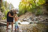Woman and child hiking across a beautiful scenic mountain river. Walking in the mountain stream on a poster