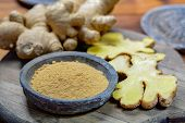 Fresh Raw Ginger Root And Bowl With Ginger Powder Close Up poster