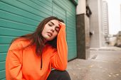 Street Portrait Of A Stylish Girl In An Orange Hoodie, Sitting On The Street And Posing On The Camer poster