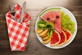 Sliced Fruit On A Wooden Background. Sliced Fruit On A Plate poster