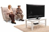 Senior couple playing video games in front of a TV isolated on white background  poster