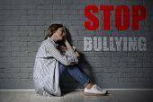 Message Stop Bullying And Sad Woman Sitting On Floor Near Brick Wall poster