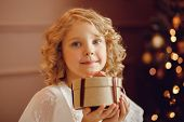 Charming Elegant European Baby With Blonde Hair And Big Blue Eyes Holds Gift In Small Round Box, On  poster