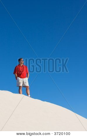 Man In Red Shirt Looking Off Into The Distance On Top Of A White Sand Dune With A Blue Sky