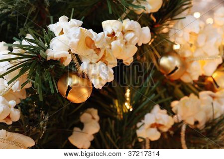 Traditional handcrafted popcorn garland (strung together with golden jingle bells) on artificial christmas tree with lights.  Macro with shallow dof.